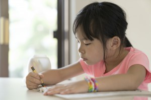 Portrait of little asian girl drawing and coloring on table