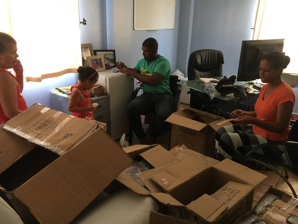Fibernetics call centre employees volunteer to unpack and sort school supplies (with some help from Peter's daughters!)