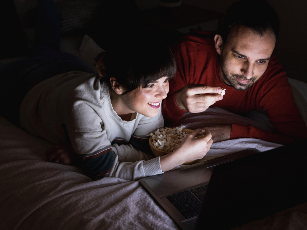 Man and woman with popcorn watching movie on laptop