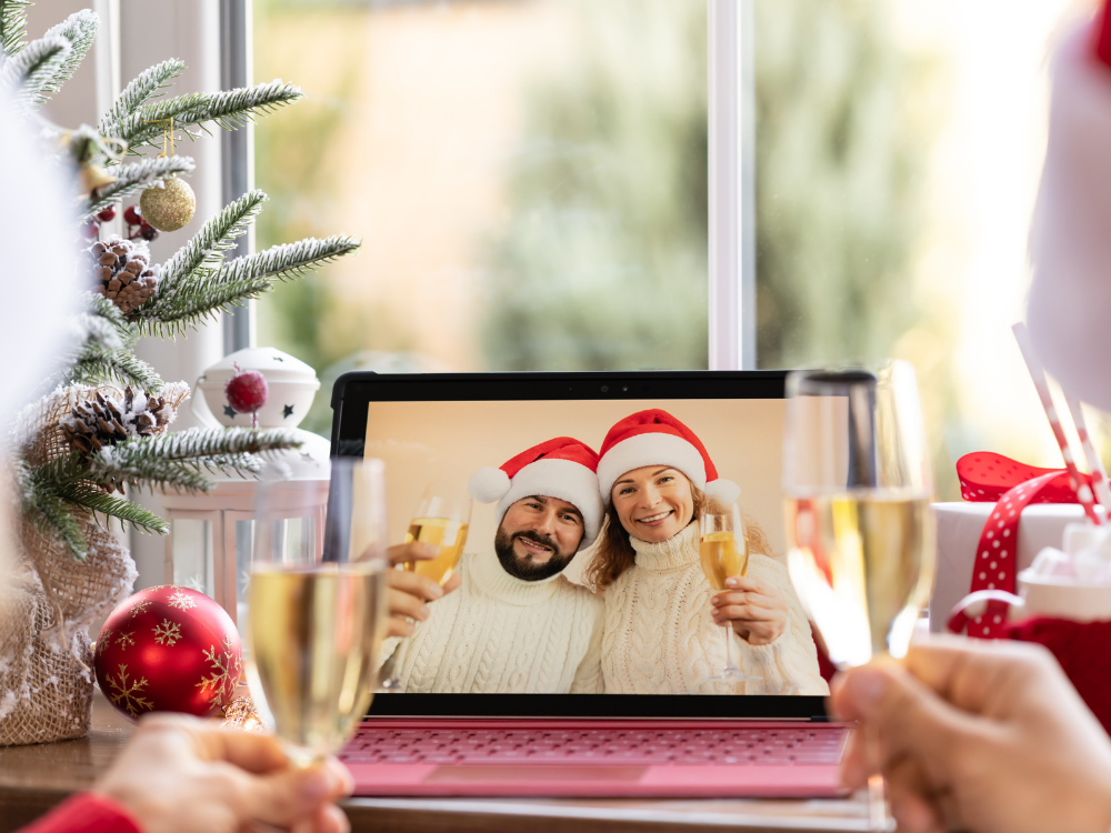 holiday decorations surround a laptop screen with man and woman on screen wearing Santa hats and toasting with champagne